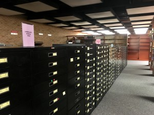 Photo of the cabinets full of microfilmed newspapers located on the second floor of the library (Madie Wilson/TBL)