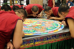 The lamas put the final touches on the mandala they have been creating all week. (TBL/Nicole Leighty)
